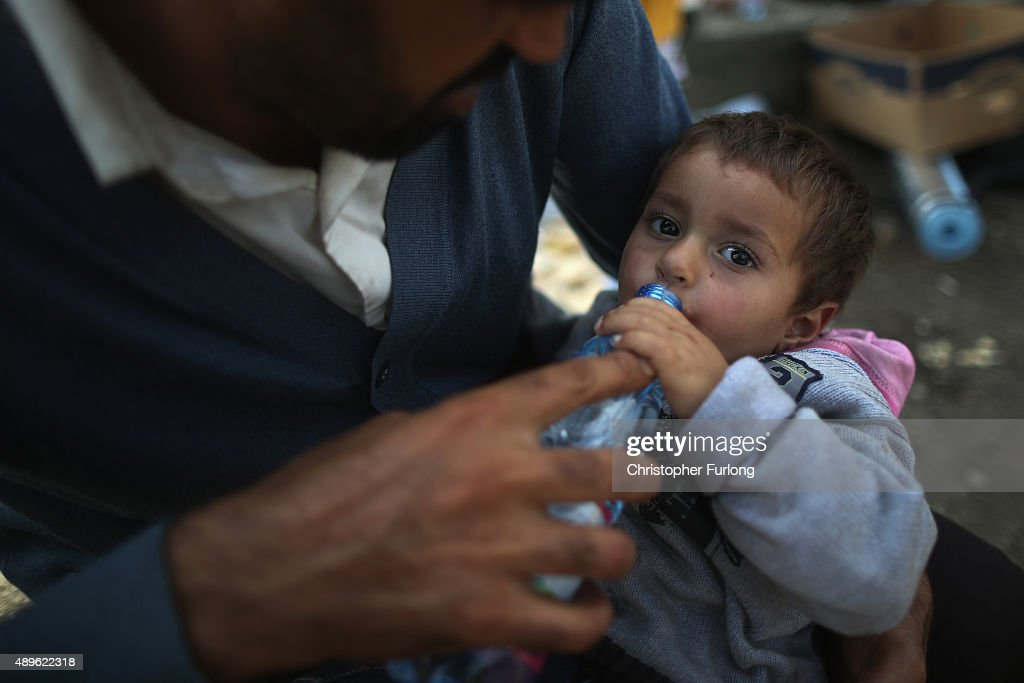 A father who arrived by train at Hegyeshalom on the Hungarian and Austrian border, gives his dehydrated son water from volunteers of the Hungarian Red Cross. They later continued their journey into Austria on September 23, 2015 in Hegyeshalom, Hungary. Thousands of migrants have arrived in Austria with more en-route from Hungary, Croatia and Slovenia. EU leaders are attending an extraordinary summit on today to try and solve the crisis.