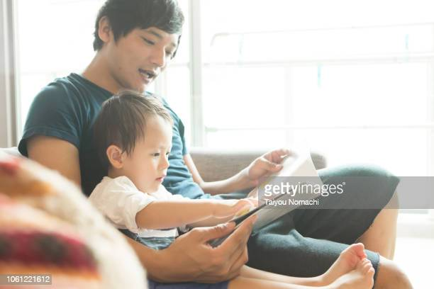 a father who reads a picture book for his son - 親 ストックフォトと画像
