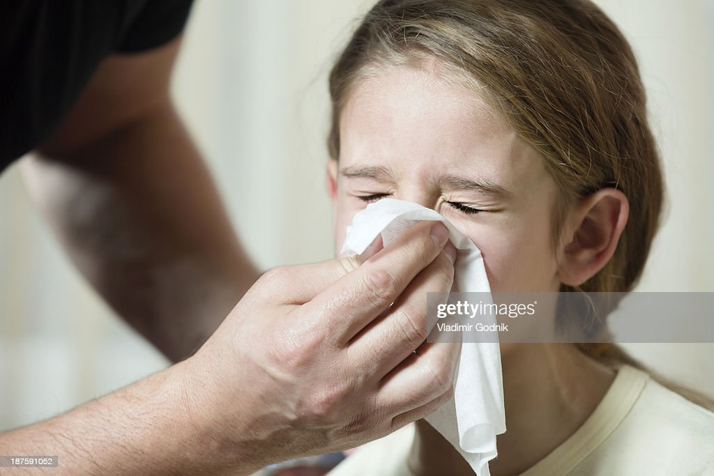 Father wiping daughter's nose with tissue : Stock Photo