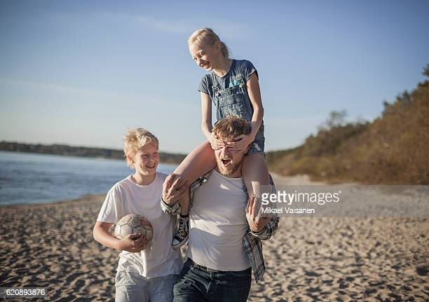 Father with 2 children having fun on the beach