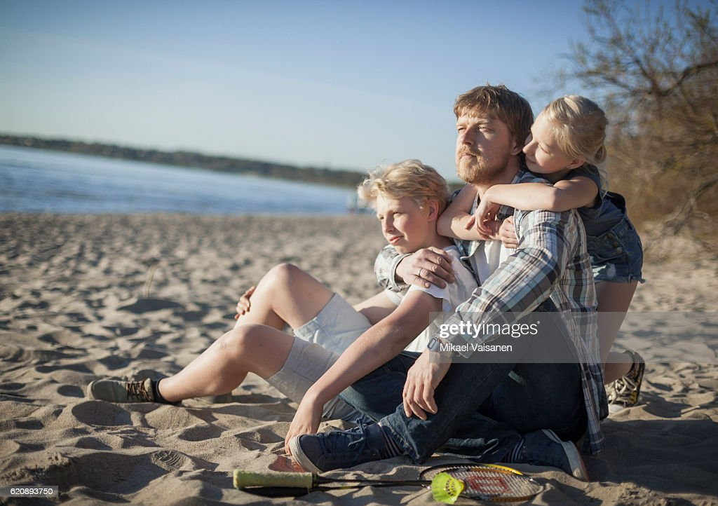 Father with 2 children relaxing on the beach : Stock Photo