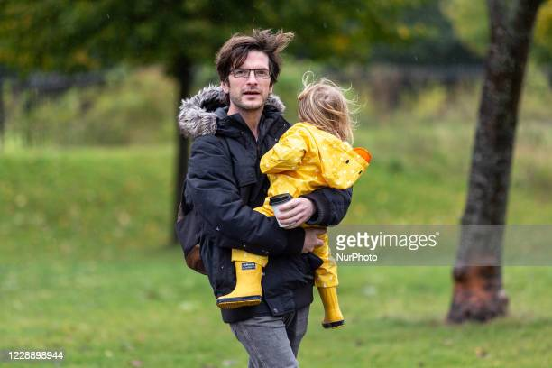 Father with a girl is seen on a rainy cold Sunday in Dulwich Park in South London, England on October 4, 2020.
