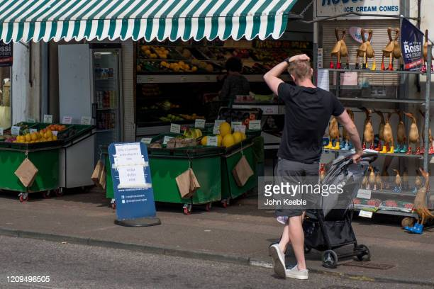 Father with a pushchair waits outside a greengrocers while the shop only lets one person in at a time on April 8, 2020 in Leigh on Sea, England....