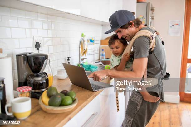 Father with a toddler in a baby carrier and a laptop in the kitchen