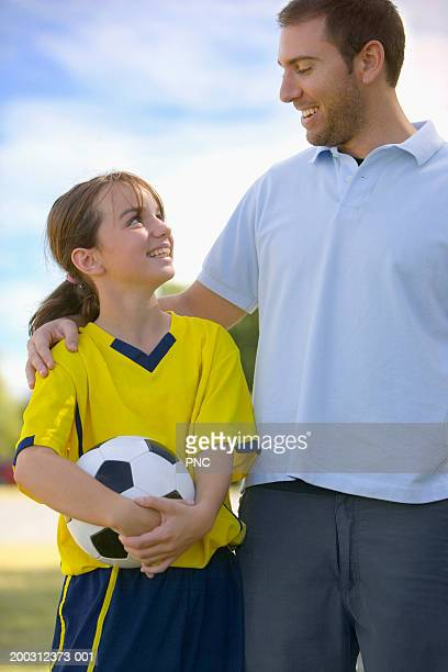 Father with arm around daughter (10-12), girl in soccer uniform