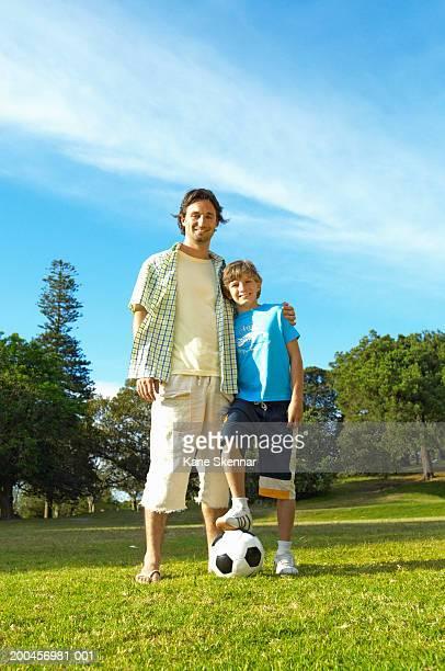 father with arm around son (10-12) in park,football on ground,portrait - 10 11 jahre stock-fotos und bilder