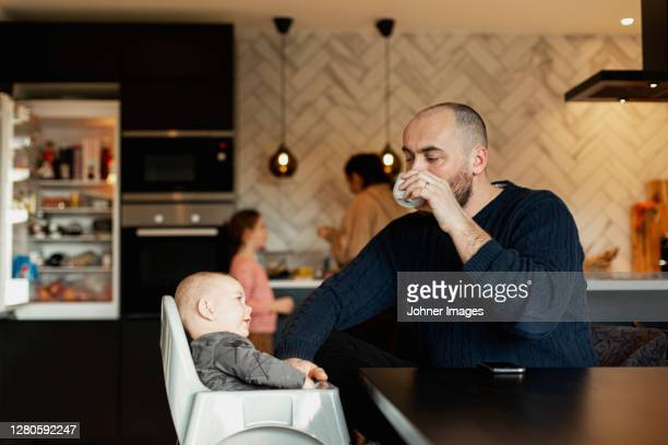 father with baby at table - paternity leave stock pictures, royalty-free photos & images