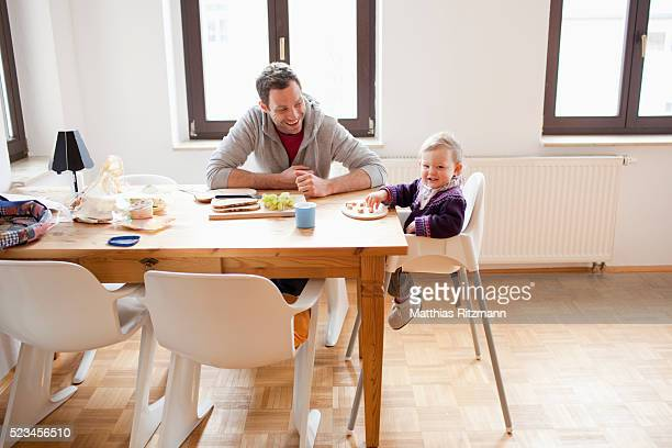 Father with baby daughter (6-12 months) sitting at table