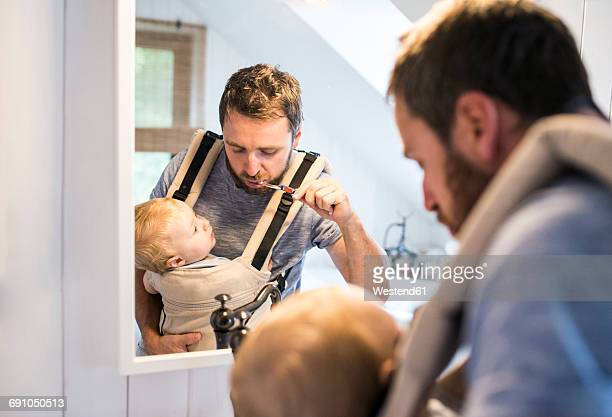 father with baby in baby carrier brushing his teeth - stay at home father stock pictures, royalty-free photos & images