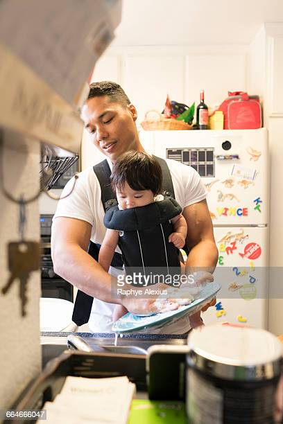 Father with baby in carrier, washing dishes