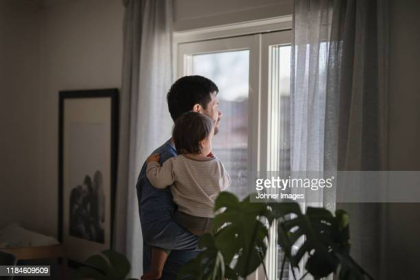 father with baby looking through window - paternity leave stock pictures, royalty-free photos & images