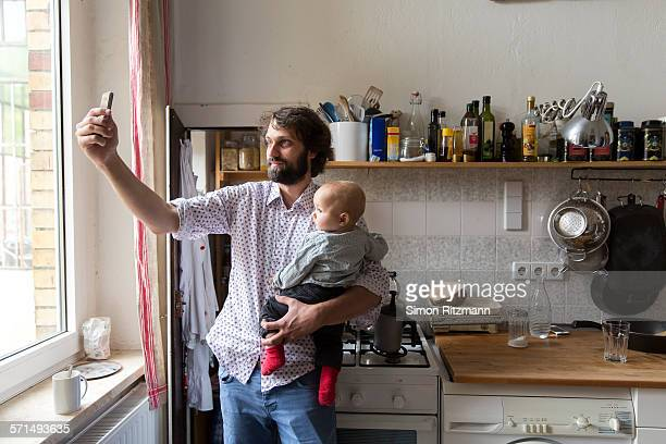 father with baby son taking selfie with smartphone - leanintogether stock pictures, royalty-free photos & images
