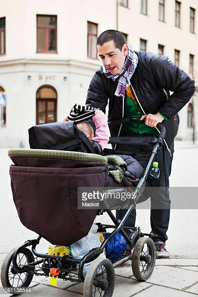 father with baby (0-11 months) stroller against built structure - 0 11 monate stock-fotos und bilder