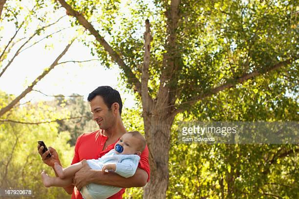 Pai com bebê com o telemóvel