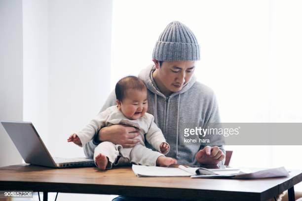 Vater mit Baby zu Hause arbeiten