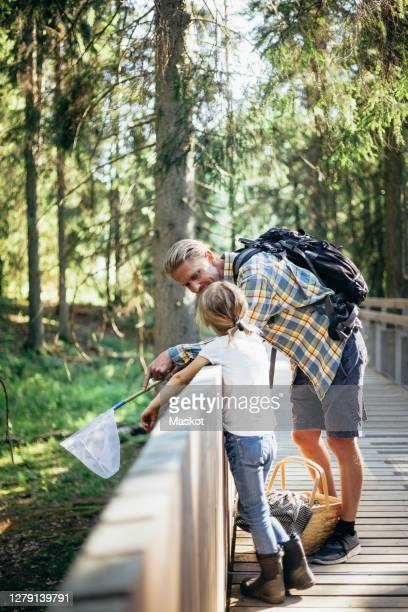 father with backpack talking to daughter on footbridge in forest - leaning stock pictures, royalty-free photos & images