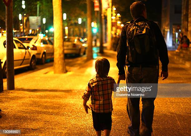 Father with boy walking in night city