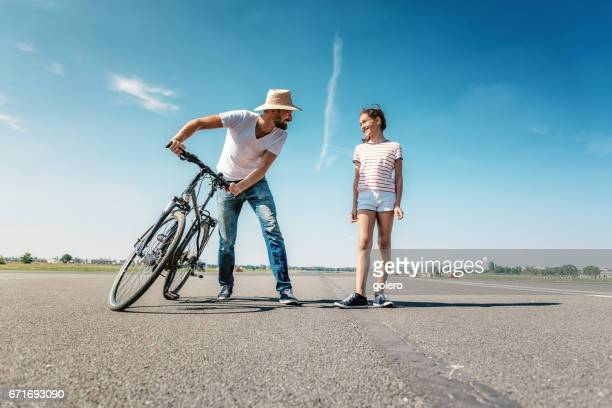 father with bycicle fooling around with teenage daughter outdoors