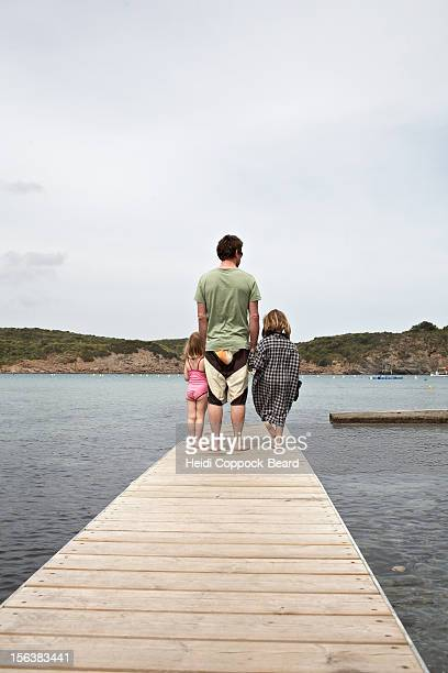 father with child at edge of jetty - heidi coppock beard fotografías e imágenes de stock