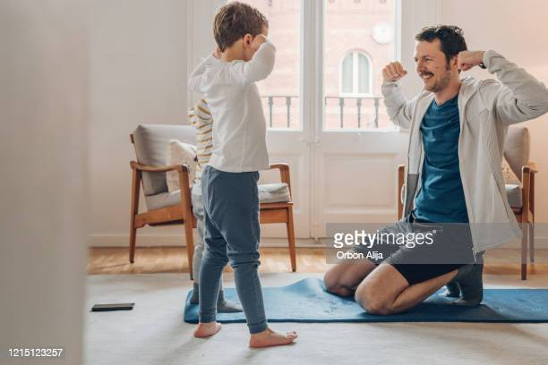 家庭で運動している子供を持つ父親 - kids weightlifting ストックフォトと画像