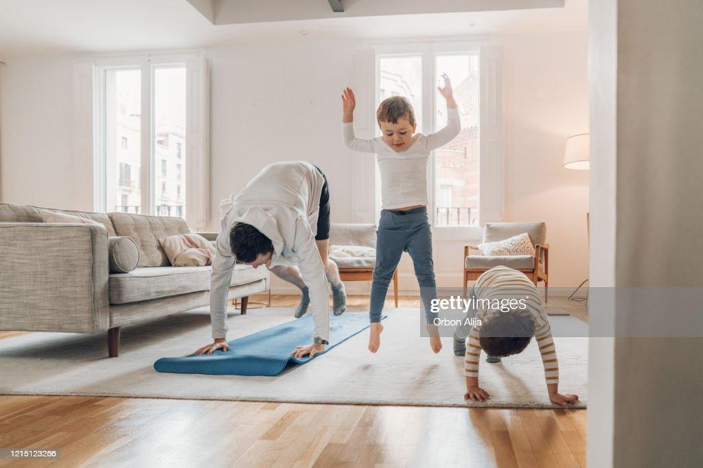 Père avec des enfants faisant l'exercice à la maison : Photo