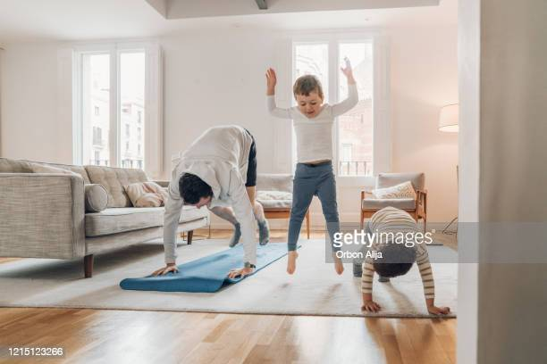father with children exercising at home - home interior stock pictures, royalty-free photos & images