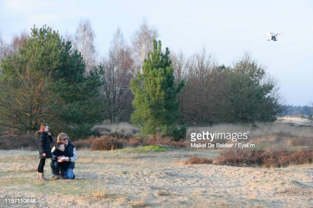 father with children flying drone in forest - remote control helicopter stock photos and pictures