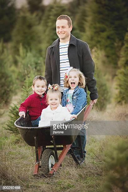 Père avec enfants dans la brouette de sapin de Noël Farm.