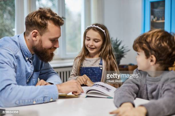 Father with children reading book at table