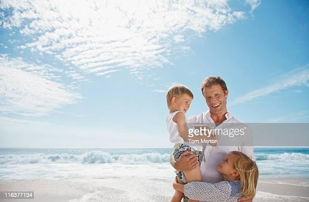 vater mit tochter und sohn am strand - alleinerzieher stock-fotos und bilder