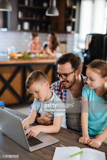 Father with daughter and son on his lap using laptop at home