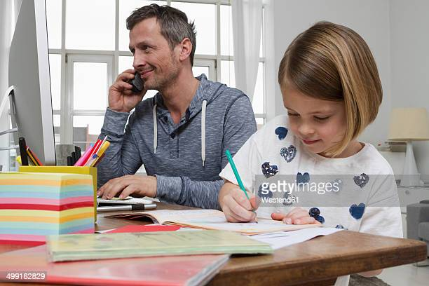Father with daughter at desk drawing