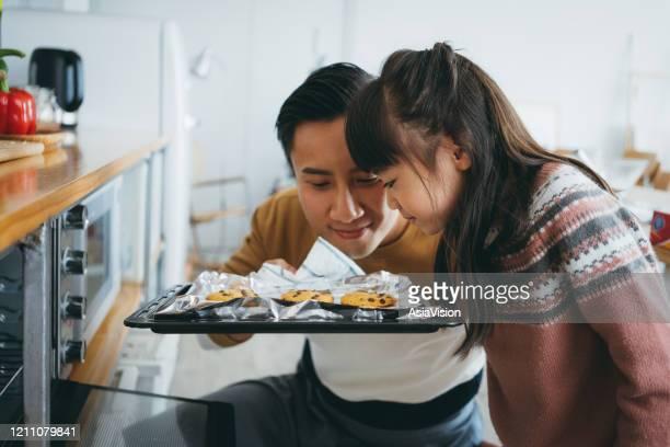 娘と一緒にキッチンでクッキーを焼き、オーブンからまっすぐ焼きたてのクッキーの香りを持つ父 - 焼く ストックフォトと画像