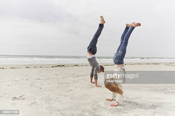 father with daughter doing a handstand on the beach - handstand stock pictures, royalty-free photos & images