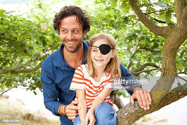 Father with daughter dressed up as pirate sitting on a tree