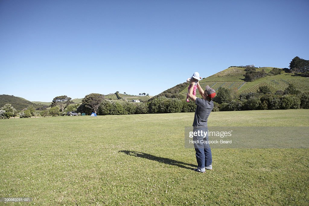 Father with daughter (3-6 months) in field : Stock Photo