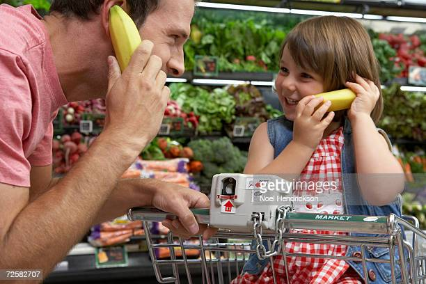 'Father with daughter (3-5) in supermarket, using bananas as telephones'