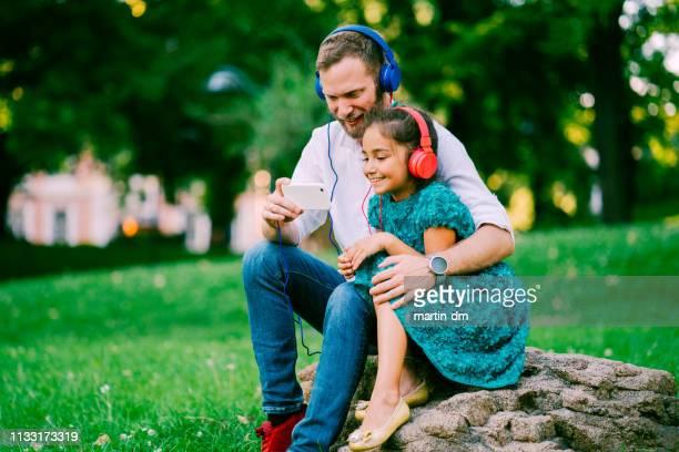 vater mit tochter im stadtpark fernsehen tv-show auf smartphone - kindertag stock-fotos und bilder