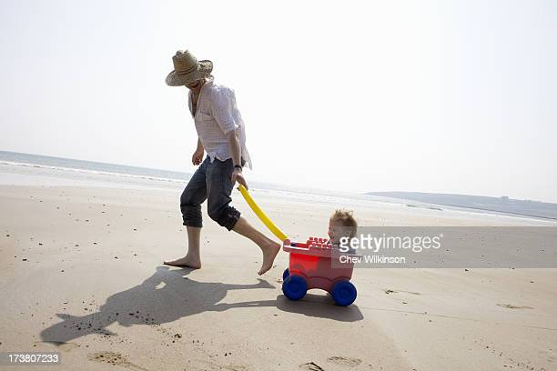 Father with daughter in wagon on beach