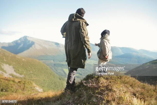 Father with daughter looking at view in mountains