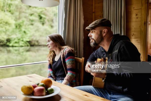 Father with daughter on a houseboat playing guitar