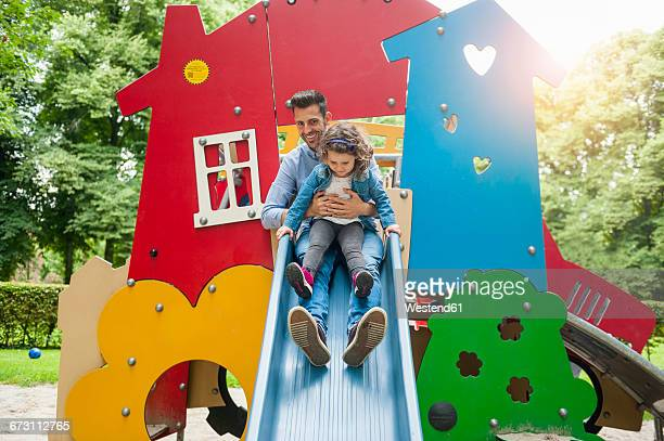 Father with daughter on playground slide