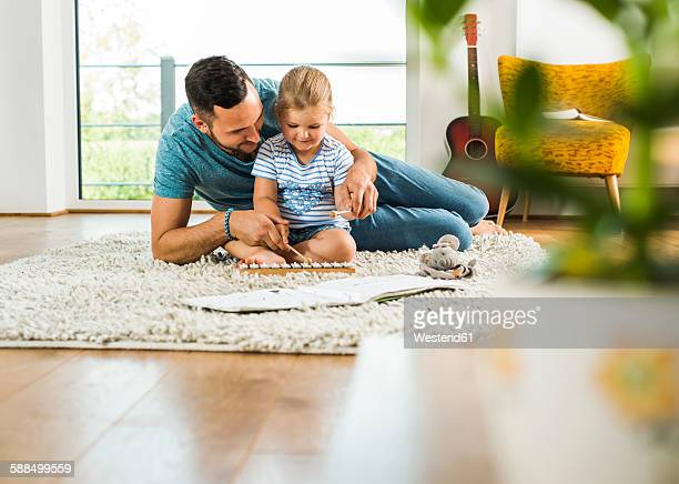 father with daughter on rug playing glockenspiel - glockenspiel stock photos and pictures