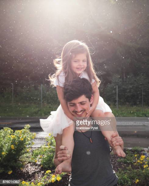 Father with daughter on shoulders having fun , rain and sun