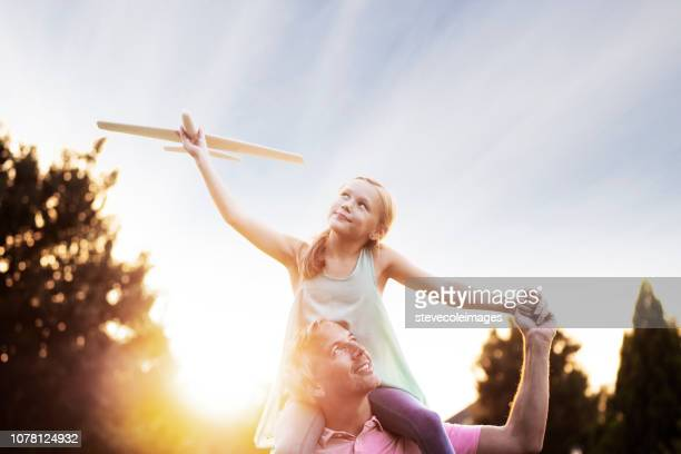 Father with Daughter on Shoulders with Model Airplane