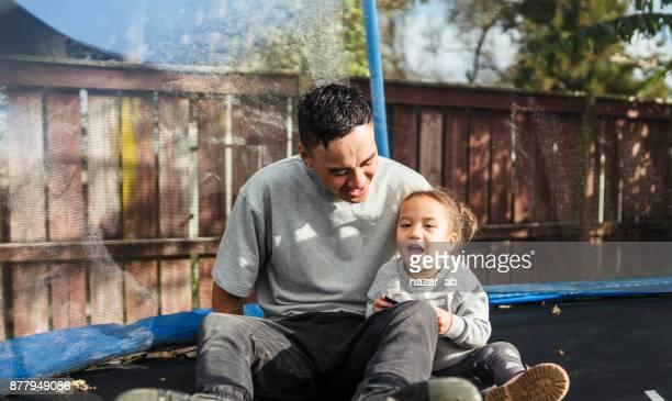 Père et fille sur trampoline.