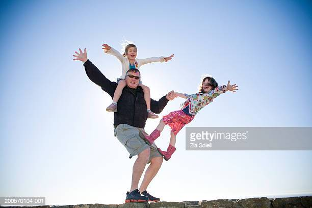 father with daughter (6-7) playing circus acrobats on wall, low angle - artist stock-fotos und bilder