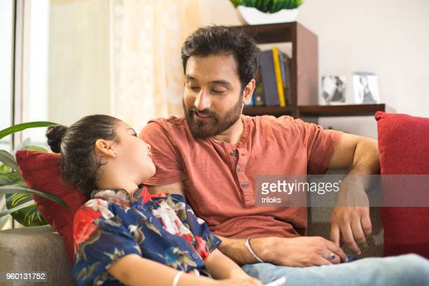 father with daughter relaxing on sofa - parent stock pictures, royalty-free photos & images