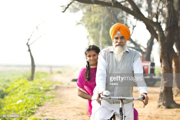father with daughter riding on bicycle - punjabi girls images stock photos and pictures