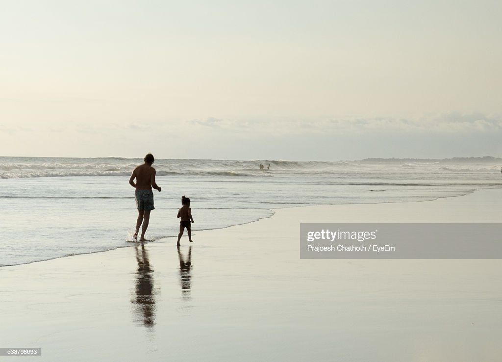 Father With Daughter Running On Beach Against Sky : Foto stock